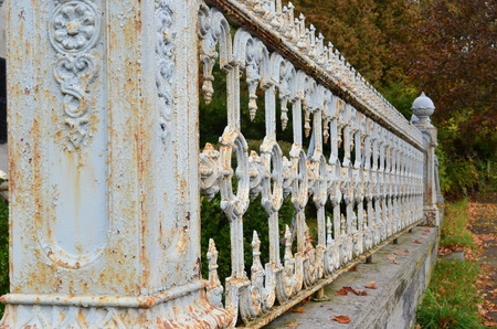 forced perspective: Forced perspective of rusty ornate fence with crackling paint Stock Photo