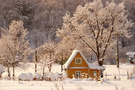 The Rose light winter morning.The Winter landscape. The Small house in snowdrift. The Snow and tree are painted in rose colour from  rising sun. Stock Photo - 2847383
