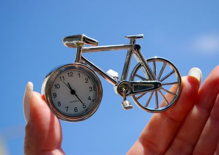 authorship: Time in hand.The Souvenir - a watch in the manner of small bicycle. The Subject is found in hand on background blue sky.The Concept : checking,  safety  for motion of time. The Bicycle-watch - a chinese product of the mass production. Authorship, marks an Stock Photo