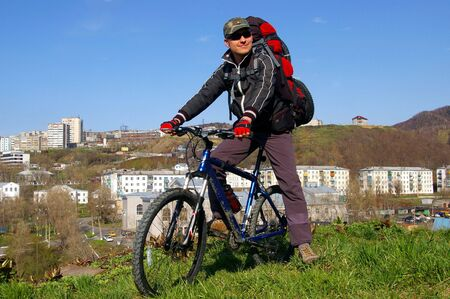 sakhalin: The Bicyclist.The Man on bicycle on background of the city. The Island Sakhalin, city Kholmsk.