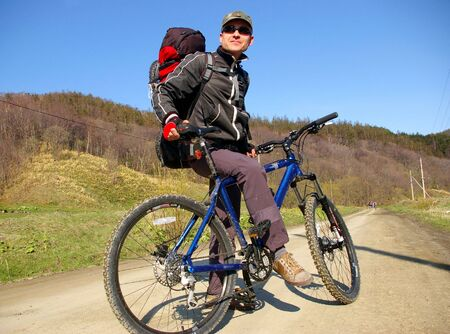 sakhalin: The Bicyclist.The Man-bicyclist on  to road, he travels on island Sakhalin. Stock Photo