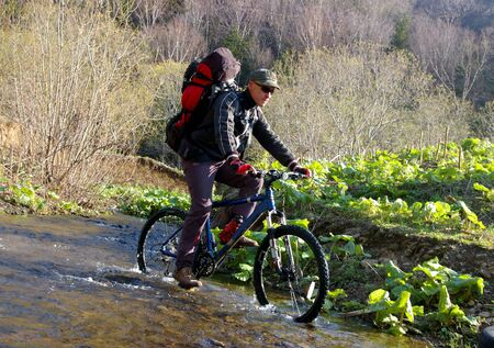 sakhalin: The Bicyclist.The Man-bicyclist moves through bugle river. The Island Sakhalin.