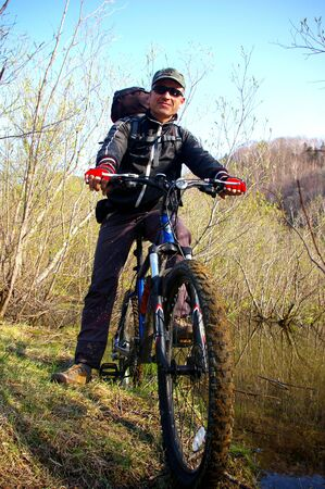 sakhalin: The Bicyclist.The Man-bicyclist travels on island Sakhalin. Ashore lake Stock Photo