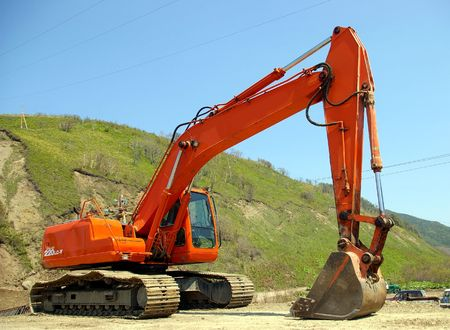 The Big caterpillar excavator of the orange colour after functioning. Stock Photo