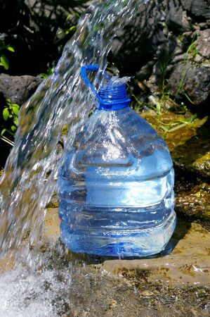 threshold: Water from the source.The Mountain creek and blue bottle with water.