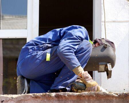 toils: Worker cuts metal Stock Photo