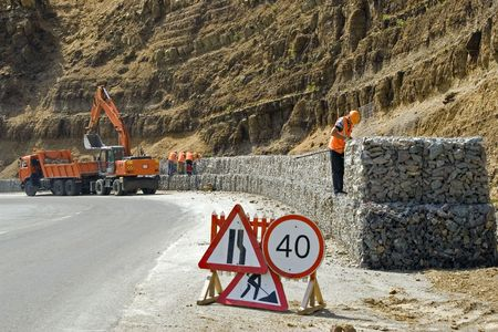 Construction stone wall under high rock - protection of the road from fall stone   Stock Photo