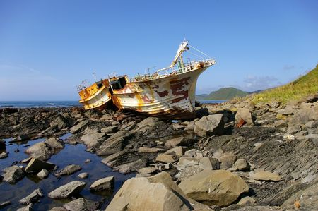 schooner: Broken fishing schooner on stone . Island Sakhalin     Stock Photo