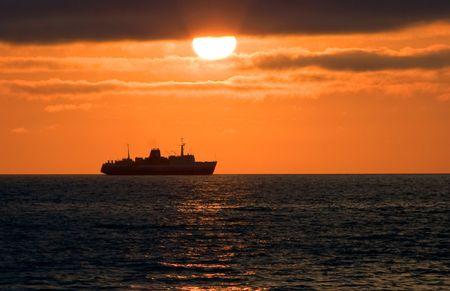 effect sunset: Sea cargo-passenger ferry on horizon during a decline (Pacific ocean)