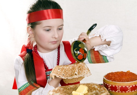 pancake week: girl in Russian national suit behind a table imposes a wooden spoon red caviar on a pancake. A pancake week.
