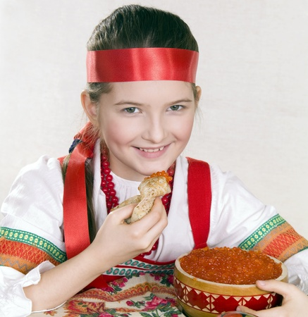 Russian girl  with   caviar and a pancake in a hand.