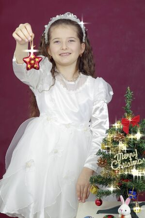 girl well-dressed holds a Christmas asterisk in a hand photo