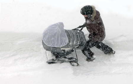 sakhalin: Father unidentified rolls the child in a baby carriage through the snowdrifts in a strong snowstorm. Kholmsk, Sakhalin Island, Russian Federation, January 7, 2015 Editorial