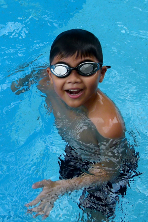 pool water: Asian kid stand in swimming pool - boy portrait with smiling Stock Photo