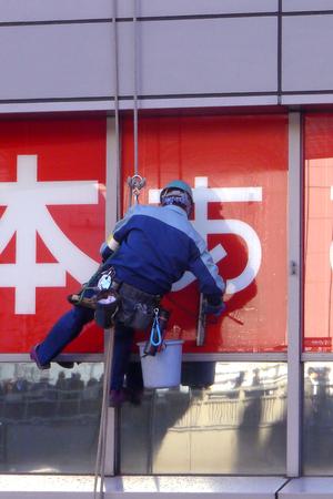 steeplejack: Window cleaner worker high to clean office glass, dangerous job high risk work