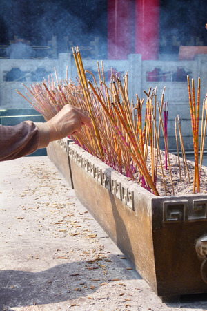 temple burn: old women burn incense stick, in front of chinese temple Stock Photo