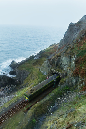 boxcar train: train pass through railway track form mountain tunnel, beside cliff of ocean