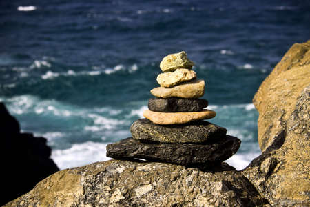 A pile of 7 stones forming a pyramid triangle shape sit on a rock on front of the ocean peacefully