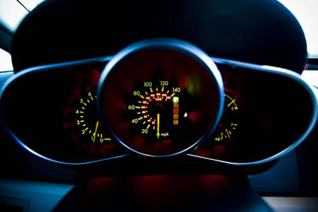 A close up of the speedometer in a car nicely glowing and lit up.