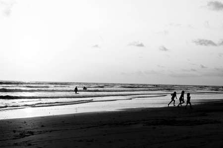 Kids playing on beach while sun is setting