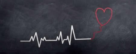 A floating heart abobe a beating heart line. Written in chalk on a blackboard Stock Photo - 6374328