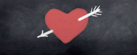A White arrow is shot through red heart. Written in chalk on a blackboard
