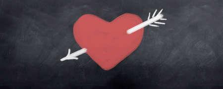 A White arrow is shot through red heart. Written in chalk on a blackboard photo