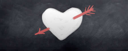 A red arrow is shot through a white heart. Written in chalk on a blackboard photo