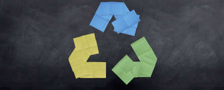 A bunch of post it notes stuck together to form the recycle sign on a blackboard.