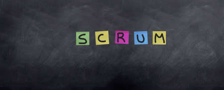 The Agile project methodology 'Scrum' is spellt on a blackboard with post it notes.