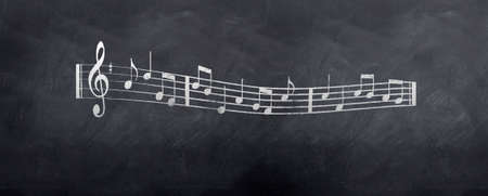 chalk board: Musical notes from sheet music sketched on a blackboard
