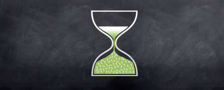 An hour glass showing dollars dropping into the lower end of the glass. Illustrating time is money. Stock Photo