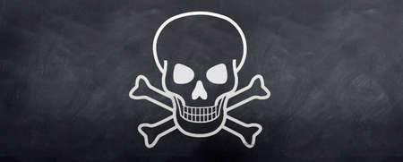 Skull and Cross bones sketched on a blackboard