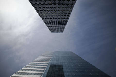 A photo taken looking up in between two modern skyscrapers in La Defense, Paris