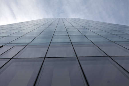 A glass background of a building stretches up tto the sky with the outline of each glass shape shown.