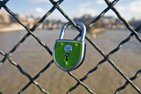 Green Lock is closed on to a fence overlooking a bridge in Paris, France