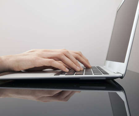 A female types fast on a laptop computer. You can also see the reflection in the table