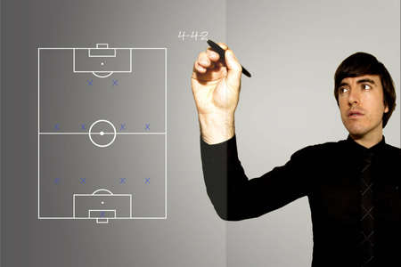 A Soccer Football Manager writes up a 4-4-2 formation on a glass pane. The famous 4-4-2 formation is the most widely used in football. Stock Photo