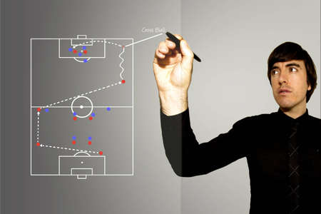 A Soccer Football Manager writes up a tactical play for a wide attacking play on a glass pane