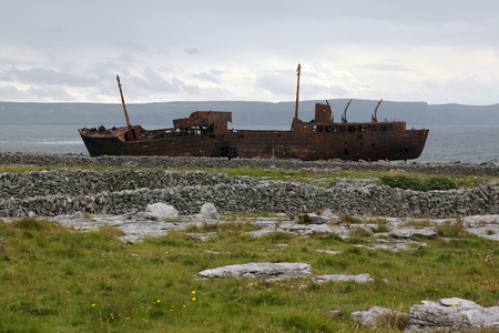Rusted remains of a freighter that washed ashore in 1960, set on a rocky beach with scenic views