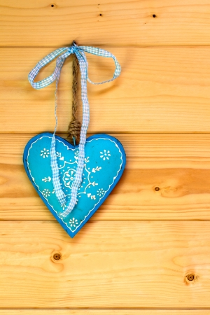 Turquoise heart on a wooden wall