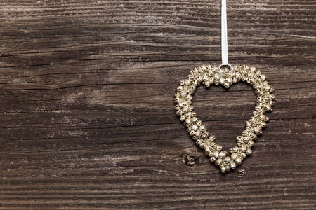 Heart made of small bells on wooden board