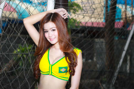 BANGKOK, THAILAND - JUNE 29, 2014  Unidentified model with Brazil costume pose for promote World Cup 2014 in futsal park on June 29, 2014 in Bangkok, Thailand