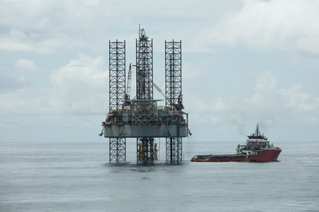 Offshore vessel alongside jack up rig in the middle of the sea