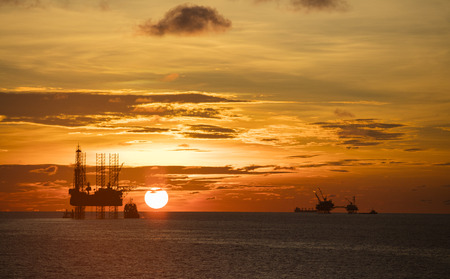 The silhouette of oil rig platform during sunset