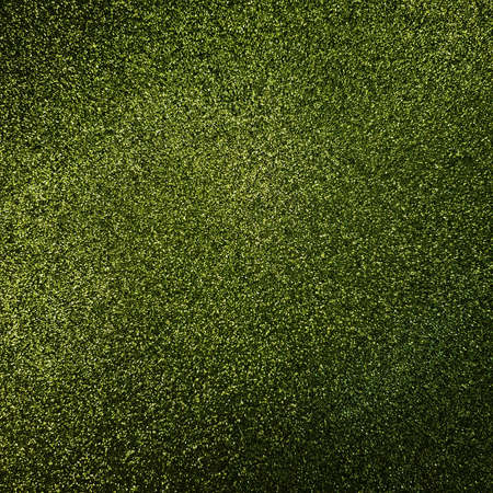 Green Glitter background. Brilliant dust abstract surface. Shimmer hologram crystal texture. Holiday sparkle backdrop.