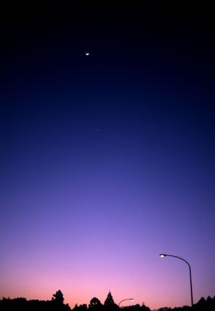 Dusk scene with colors from pink to deep blue with speck of moon photo