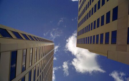 Looking up at clouds and blue sky between two skyscrapers in New Orleans Stock Photo