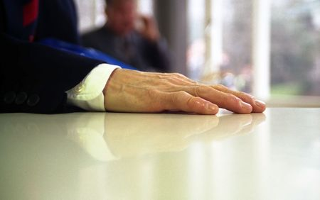 table: Close up of hand of business man resting on a table, with out of focus man talking on phone in background Stock Photo