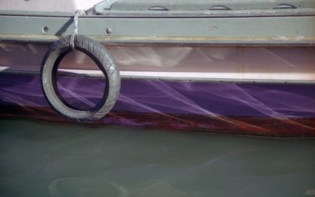 Close view of side of boat with tire in Venice, Italy. Stock Photo